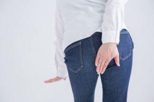 白いシャツ・インディゴブルーのジーンズを履いた女性の後ろ姿。お尻に片手を当てている。