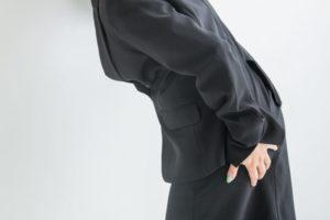 黒いスーツ姿の女性が片手でお尻に手を当てながら前かがみの姿勢をとっている