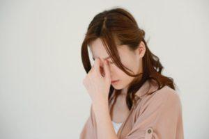 眉間にしわを寄せ、目頭を手でつかんでいる女性。
