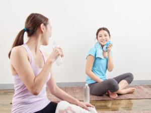 ヨガがひと段落ついてい水分をとりながら談笑する二人の若い女性達。手ぬぐいで汗をふきながら、一仕事終えたという表情。