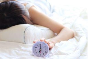 うつ伏せ寝の状態で手にはアナログ式の白色の目覚まし時計をもっている。