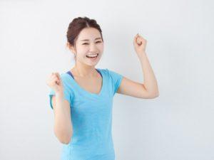 Vネックの水色のTシャツ姿の女性が両手で笑顔でガッツポーズをとっている。