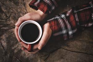 チェックシャツの肘より先の手だけが移っており、両手でブラックコーヒーを包み込むようにもっている。