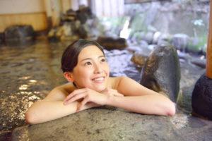 若い女性が温泉で方からさきを湯船の中から出し、嬉しそうな表情で上を見つめている。