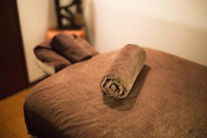 もみほぐしを受けるのため茶色ののベッドと、茶色のバスタオル1枚が丸められている。