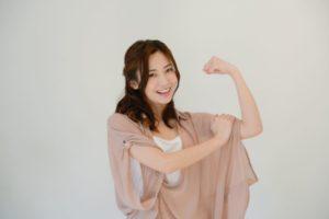 片手の力こぶ付近にもう一方の手をのせて、筋肉があることをアピールしようとしている。年齢は20代後半で橙色の清楚な洋服。