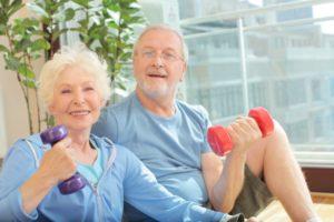 ご高齢のご夫婦と思われる2人が片手にそれぞれダンベルを持ち、座り姿勢で笑顔で楽しそう。