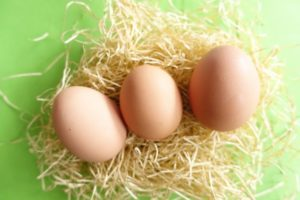 3つの黄褐色の卵が黄緑色のボードのうえに置かれえている