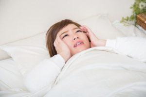 ベッドのうえで仰向けになり、両手にこめかみを押さえて「不眠」の症状で悩ましそうにしている