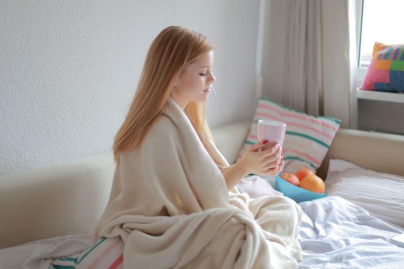 ベッドソファーの上でブロンドの若い女性が薄い毛布を肩から掛け、飲み物を両手でもっている