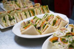 テーブルの上の白いお皿の上に沢山の三角形に切られたサンドイッチが置かれている
