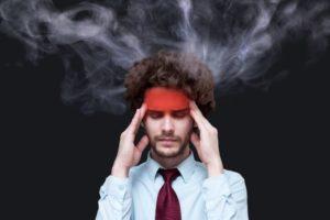 髭を生やしている外国人男性が、赤みを帯びたおでこの側面のこめかみを両手で押さえ、頭からは湯気が出ている