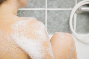 入浴中の女性。背中と足の一部が写っており白い泡に包まれている