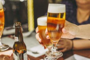 複数人とビールを手に乾杯しようしていしる瞬間