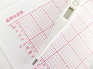 基礎体温表の上に体温計が置かれている
