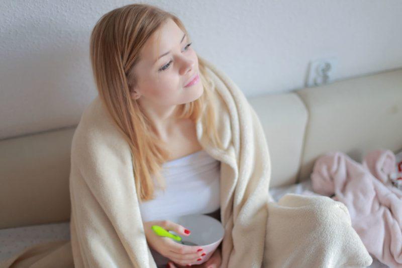 毛布を肩から掛けソファーの上でくつろいでいるブロンドの女性